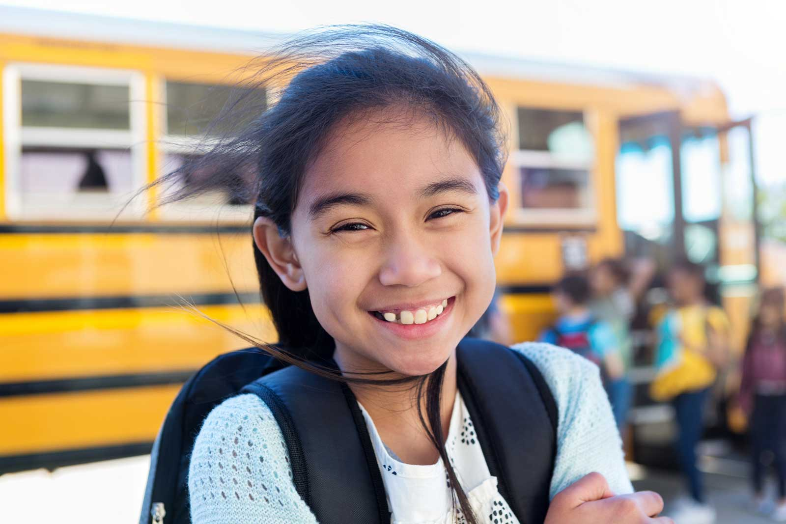 A happy elementary-aged school girl is getting on a school bus for the first day of school.